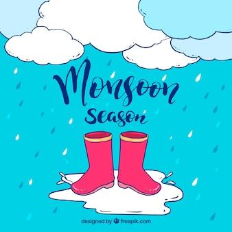 Fondo di stagione dei monsoni con stivali d'acqua