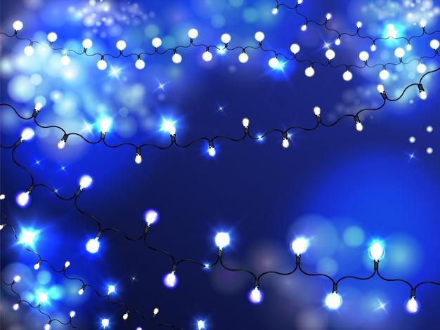 Fondo luminoso della ghirlanda di illuminazione di festa con le lampadine accese e brillanti su corda