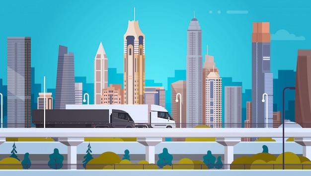 Fondo moderno del paesaggio della città con i veicoli dei rimorchi del camion dei semi sulla strada della strada principale