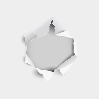 Foro strappato e strappato in foglio di carta su uno sfondo grigio