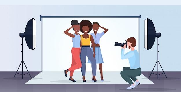 Fotografo professionista che usa l'uomo della macchina fotografica che spara bei modelli sexy delle donne che posano integrale orizzontale interno dello studio fotografico moderno