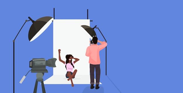Fotografo professionista che utilizza l'uomo della macchina fotografica che spara le mani sollevanti di modello della bella donna sexy che posano nell'illustrazione integrale orizzontale dello studio moderno della foto