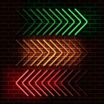 Frecce al neon verde, giallo e rosso su un muro di mattoni