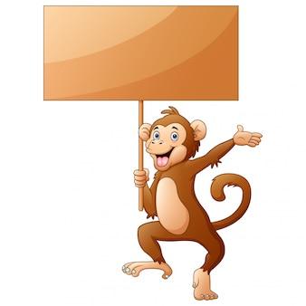 Fumetto della scimmia che tiene un segno di legno su fondo bianco