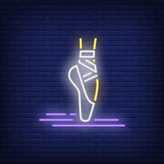 Gamba della donna che indossa l'insegna al neon della scarpa di balletto del pointe