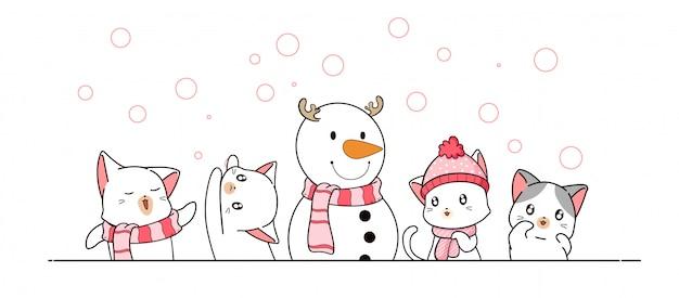 Gatti e pupazzo di neve dell'insegna nel giorno di inverno