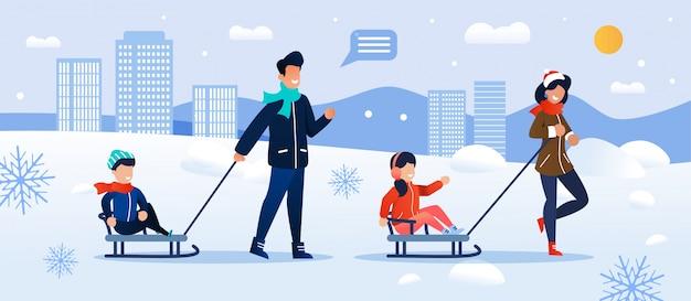 Genitori felici che sledding i bambini a winter park