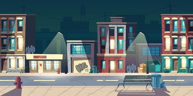 Ghetto street di notte, baraccopoli, vecchi edifici con finestre luminose e graffiti sui muri. le abitazioni dilapidate stanno sul bordo della strada con le lampade, gli idranti antincendio, illustrazione di vettore del fumetto dei bidoni della spazzatura