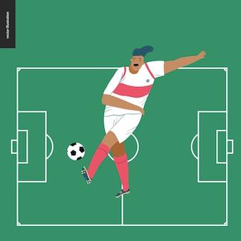 Giocatore di calcio europeo di calcio che dà dei calci ad un pallone da calcio nel campo di football americano verde