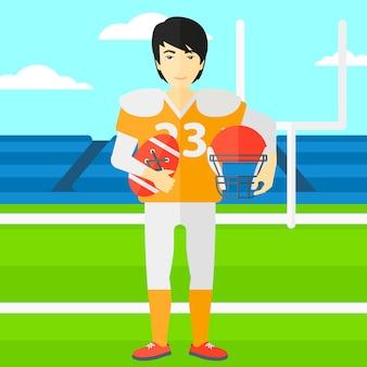 Giocatore di rugby con palla e casco in mano.