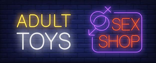 Giocattoli per adulti nell'insegna al neon del sexshop. simboli di genere che si uniscono nell'angolo del cartello.