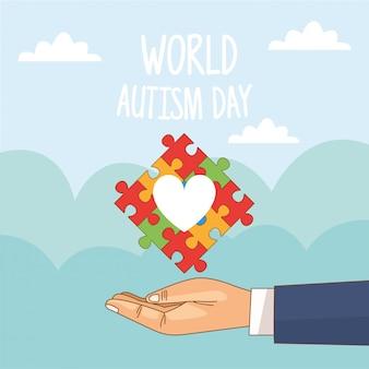 Giornata mondiale dell'autismo con il cuore di puzzle di sollevamento della mano