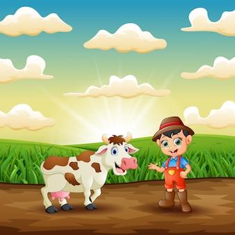 Giovane agricoltore con la sua mucca nel campo