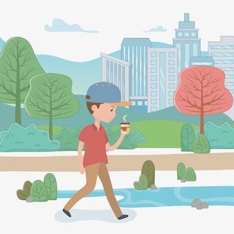 Giovane che cammina con il caffè nel parco