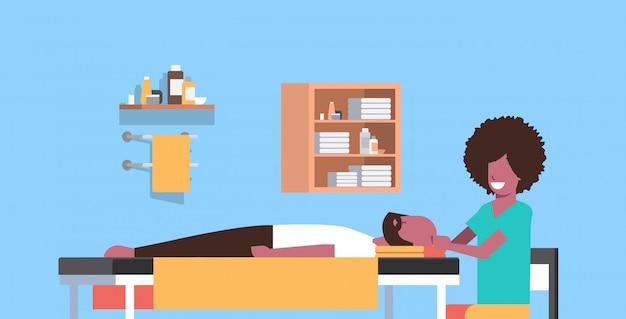 Giovane che ha massaggiatrice di massaggio capo che massaggia la distensione di rilassamento del tipo paziente del corpo paziente sul concetto di lusso di concetto del trattamento del salone della stazione termale della tavola