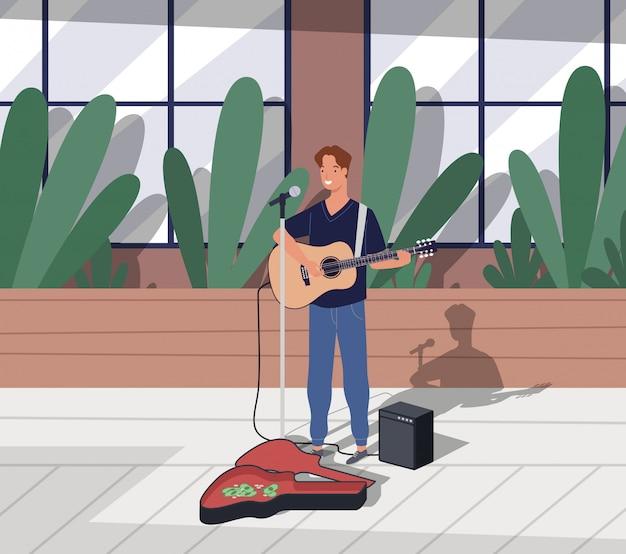 Giovane chitarrista maschio felice in piedi e suonando per suonare la chitarra sulla strada della città. il personaggio dell'uomo di strada interpreta la canzone