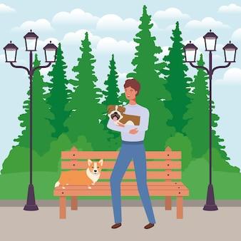 Giovane con le mascotte dei cani svegli nel parco