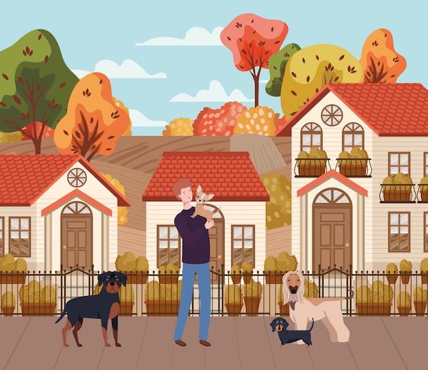 Giovane con le mascotte dei cani svegli nella scena della città di autunno