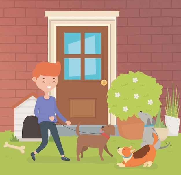 Giovane con le mascotte dei piccoli cani nel giardino della casa