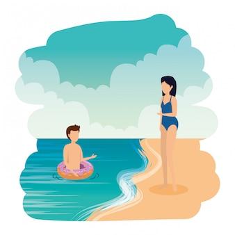 Giovane coppia con galleggianti sulla spiaggia