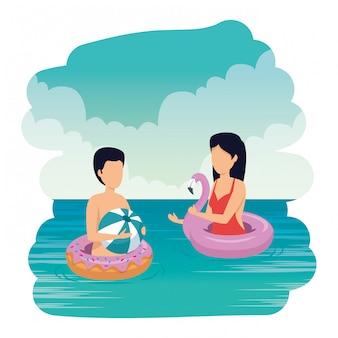 Giovane coppia con palloncino e galleggiante sulla spiaggia