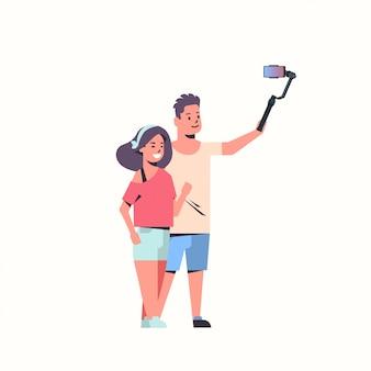 Giovane coppia utilizzando selfie stick amanti prendendo foto su smartphone fotocamera uomo donna divertirsi maschio femmina personaggi dei cartoni animati sfondo bianco integrale