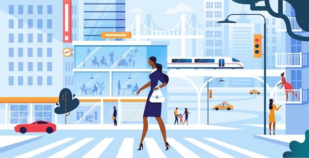Giovane donna adorabile in vestito alla moda che cammina lungo l'attraversamento pedonale in grande metropoli occupata, stile di vita di ragazza city dweller, fretta al lavoro o tempo libero di fine settimana