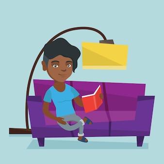 Giovane donna africana che legge un libro sul sofà.