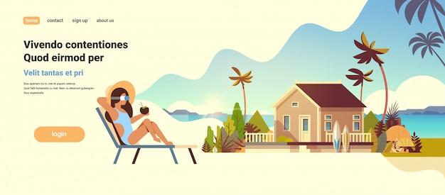 Giovane donna bikini indossare occhiali digitali seduto sdraio lettino realtà virtuale visione villa casa tropicale spiaggia vacanze estive concetto piatta