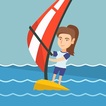 Giovane donna caucasica che fa windsurf nel mare.