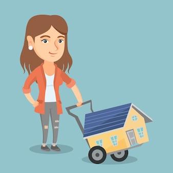 Giovane donna caucasica con una casa su un carrello.