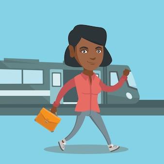 Giovane donna che cammina su una piattaforma della stazione ferroviaria.