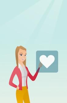 Giovane donna che preme bottone a forma di cuore.