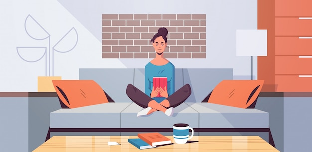 Giovane donna che si siede sullo strato facendo uso del concetto di e-learning del libro elettronico della lettura della ragazza della compressa moderno