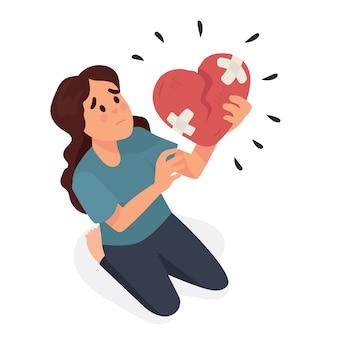 Giovane donna che tiene un cuore spezzato