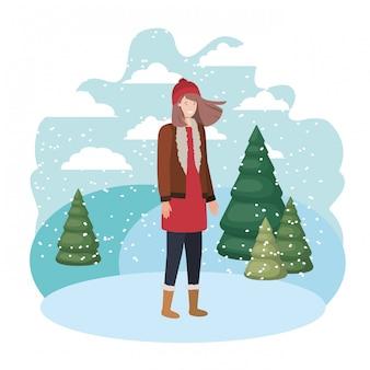 Giovane donna con abiti invernali e pini invernali