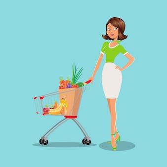 Giovane donna con il carrello pieno di frutta e verdura nel supermercato.