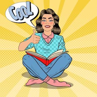 Giovane donna graziosa di pop art che si siede e che legge il libro con il pollice del segno della mano. illustrazione