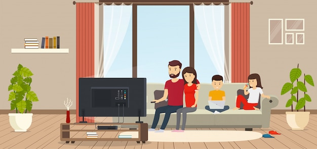 Giovane famiglia a casa seduto sul divano, guardare la tv, bambino che lavora al computer portatile, figlia che mangia il gelato. moderna sala interna con finestre panoramiche.