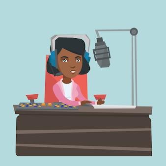 Giovane femmina afroamericana dj che lavora alla radio.