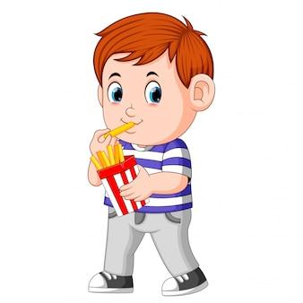 Giovane ragazzo che mangia le patate fritte