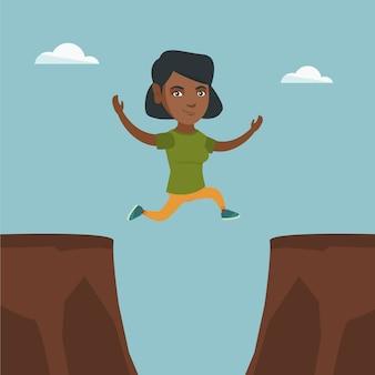 Giovane sportiva africana che salta sopra la scogliera
