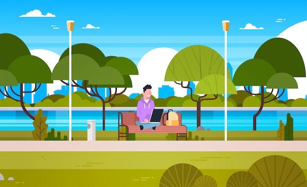 Giovane tipo in parco che per mezzo del computer portatile all'aperto sedendosi sul banco