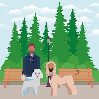 Giovane uomo afro con mascotte di cani svegli nel parco