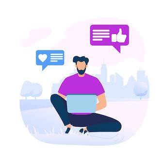 Giovane uomo barbuto che si siede sulla terra con il computer portatile