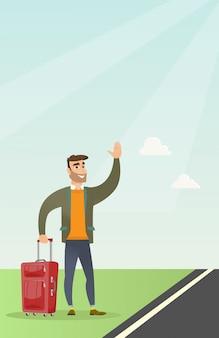Giovane uomo caucasico con la valigia autostop.