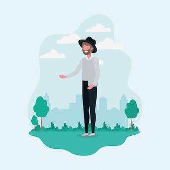 Giovane uomo con barba e cappello in piedi nel carattere del parco