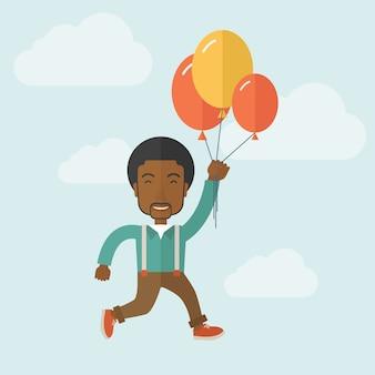 Giovane uomo di colore che vola con palloncini.