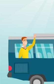 Giovane uomo indoeuropeo agitando la mano dalla finestra del bus.