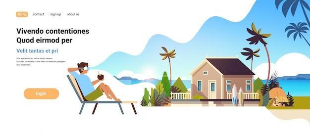 Giovane uomo indossare occhiali digitali seduto sdraio lettino realtà virtuale visione villa casa tropicale spiaggia vacanze estive concetto piatta